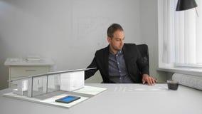 L'uomo d'affari sta esaminando l'architettura di un modello moderno della casa sporgente e stampato dalla realtà mista futuristic archivi video