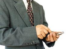 L'uomo d'affari sta giocando il cellulare Immagini Stock