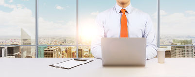 L'uomo d'affari sta lavorando con il computer portatile Ufficio o posto di lavoro panoramico moderno con la vista di New York Cit Immagini Stock Libere da Diritti