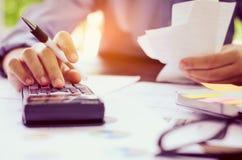 L'uomo d'affari sta lavorando con un calcolatore e un computer portatile In ufficio Immagine Stock