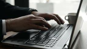 L'uomo d'affari sta scrivendo sulla tastiera del computer portatile archivi video