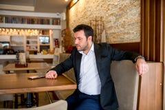L'uomo d'affari sta sedendosi nel ristorante e nell'attesa immagini stock