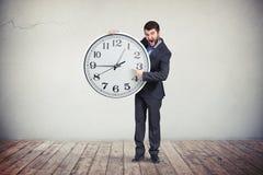 L'uomo d'affari sta sottolineando sul tempo sul grande orologio Fotografie Stock Libere da Diritti