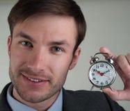 L'uomo d'affari sta tenendo una sveglia fotografia stock libera da diritti