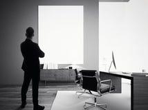 L'uomo d'affari sta in ufficio moderno con tela bianca vuota BW immagini stock
