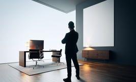 L'uomo d'affari sta in ufficio moderno con tela vuota colore immagini stock libere da diritti