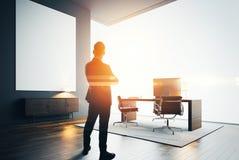 L'uomo d'affari sta in ufficio moderno con una tela vuota Effetti di Bokeh fotografie stock libere da diritti