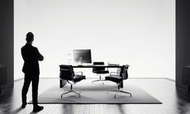L'uomo d'affari sta in ufficio moderno e nell'esame dell'orizzonte BW fotografie stock