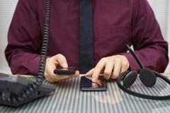L'uomo d'affari sta utilizzando due telefoni cellulari e telefoni della linea terrestre a Immagini Stock Libere da Diritti
