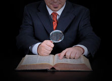 L'uomo d'affari sta utilizzando la lente d'ingrandimento Fotografia Stock Libera da Diritti