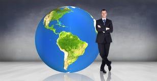 L'uomo d'affari sta vicino alla grande palla della terra Immagini Stock