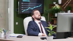 L'uomo d'affari stanco è caduto addormentato nel suo luogo di lavoro video d archivio