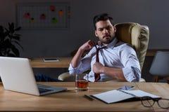 l'uomo d'affari stanco allenta il legame e la seduta alla tavola con vetro Immagini Stock