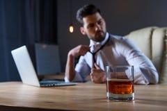 l'uomo d'affari stanco allenta il legame e la seduta alla tavola con vetro di whiskey Fotografia Stock