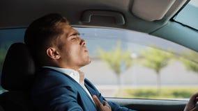 L'uomo d'affari stanco e sollecitato sta sedendosi nell'automobile Uomo che ha emicrania Sforzo, fallimento, cattive notizie, dol video d archivio