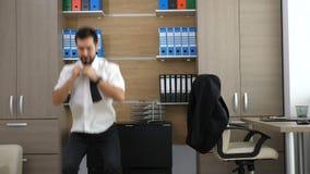 L'uomo d'affari stanco nell'ufficio sta prendendo una rottura praticando la scatola nell'ufficio archivi video