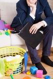 L'uomo d'affari stanco pulisce il disordine nella casa Immagini Stock