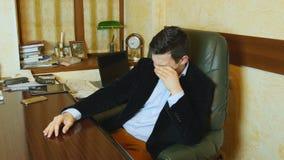 L'uomo d'affari stanco sta lavorando Immagine Stock