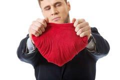 L'uomo d'affari strappa il cuscino a forma di cuore Fotografia Stock Libera da Diritti