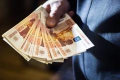 L'uomo d'affari tiene un grande pacco di soldi in sua mano Immagine Stock Libera da Diritti