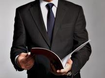 L'uomo d'affari tiene un libretto fotografie stock