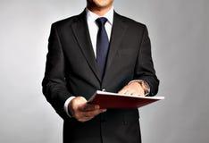 L'uomo d'affari tiene un libretto fotografia stock libera da diritti