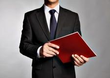 L'uomo d'affari tiene un libretto Immagine Stock