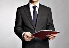 L'uomo d'affari tiene un libretto immagine stock libera da diritti