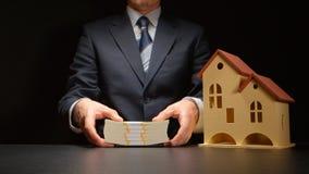 L'uomo d'affari tiene una pila dei soldi vicino ad un modello della casa su una tavola Immagini Stock Libere da Diritti