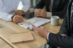 L'uomo d'affari tre che esamina il grafico in carta e parla del business plan, dell'introduzione sul mercato e di finanziario in  Immagine Stock Libera da Diritti