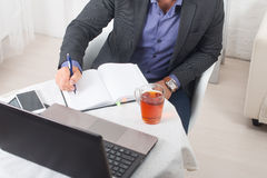 L'uomo d'affari in ufficio che si siede ad una tavola con un computer portatile scrive con concentrazione Fotografia Stock