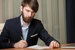 L'uomo d'affari in ufficio firma il documento Fotografia Stock