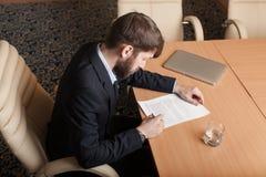L'uomo d'affari in ufficio firma il documento Immagine Stock Libera da Diritti