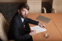 L'uomo d'affari in ufficio firma il documento Fotografia Stock Libera da Diritti