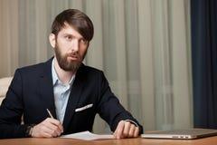 L'uomo d'affari in ufficio firma il documento Immagini Stock Libere da Diritti