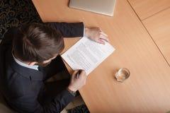 L'uomo d'affari in ufficio firma il documento Fotografie Stock Libere da Diritti