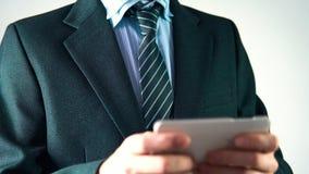 L'uomo d'affari in un vestito alla moda con un legame utilizza un telefono elegante, uomo di affari archivi video