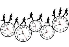 L'uomo d'affari in una fretta funziona sugli orologi di tempo Fotografie Stock Libere da Diritti