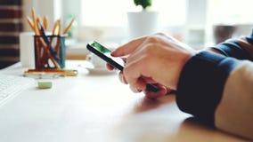 L'uomo d'affari utilizza uno smartphone nell'ufficio nel luogo di lavoro stock footage