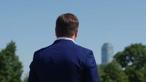 L'uomo d'affari in vestito blu sta esaminando fuori la distanza su un grattacielo dell'ufficio 4K video d archivio