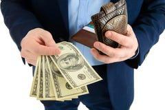 L'uomo d'affari in vestito elimina il dollaro dal portafoglio, contanti della tenuta della mano, primo piano Fotografia Stock