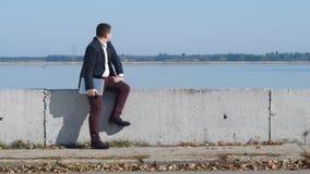 L'uomo d'affari in vestito si siede dal fiume ed esamina il tempo stock footage