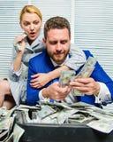 L'uomo d'affari vicino ai dollari dei contanti usufruisce Concetto enorme di profitto girl finanziario tiene un pacchetto di piac fotografie stock