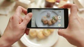 L'uomo d'avanguardia in un ristorante fa la foto di alimento con la macchina fotografica del telefono cellulare stock footage
