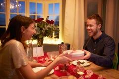 L'uomo dà il regalo della donna al pasto romantico del giorno di biglietti di S. Valentino Fotografia Stock Libera da Diritti