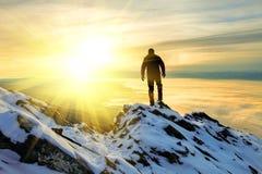 L'uomo da stare sulla cima della montagna ad alba Fotografie Stock Libere da Diritti