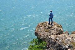 L'uomo dai capelli grigio spara il video che sta su una roccia alta sopra il mare blu Fotografia Stock Libera da Diritti