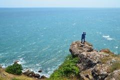 L'uomo dai capelli grigio spara il video che sta su una roccia alta sopra il mare blu Immagini Stock Libere da Diritti