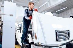 L'uomo dai capelli rossi lavora al servizio automatico Il meccanico è impegnato nella riparazione dell'automobile Fotografia Stock