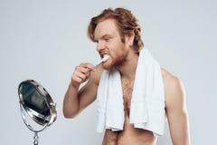 L'uomo dai capelli rossi sta pulendo i denti Fotografia Stock Libera da Diritti